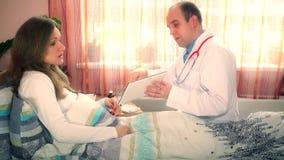 Soignez l'homme montrant la tablette numérique parlant avec la jeune femme patiente banque de vidéos