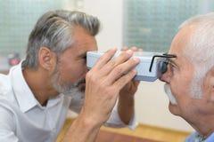Soignez l'optométriste au travail avec le dispositif pour examiner la vision images stock