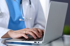 Soignez la dactylographie sur l'ordinateur portable tout en se reposant au bureau en verre dans le bureau d'hôpital Médecin au tr images libres de droits