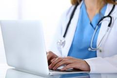 Soignez la dactylographie sur l'ordinateur portable tout en se reposant au bureau en verre dans le bureau d'hôpital Médecin au tr photographie stock