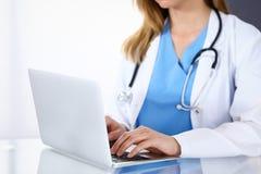 Soignez la dactylographie sur l'ordinateur portable tout en se reposant au bureau en verre dans le bureau d'hôpital Médecin au tr image stock