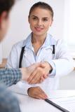 Soignez la femme souriant tout en serrant la main à son patient masculin Concept de médecine et de confiance Photographie stock libre de droits