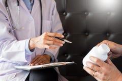 Soignez la main tenant le comprimé de la drogue et l'expliquez au patient dans ho image libre de droits