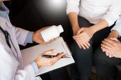 Soignez la main tenant le comprimé de la drogue et l'expliquez au patient dans ho image stock