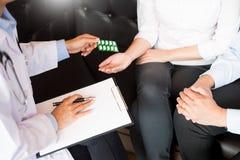Soignez la main tenant le comprim? de la drogue et l'expliquez au patient dans la chambre d'h?pital image libre de droits