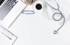 Soignez la table de bureau avec le stéthoscope, café, robe médicale et pas Photographie stock libre de droits