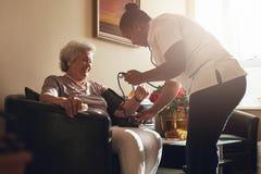 Soignez la tension artérielle de mesure du patient supérieur dans la retraite h Photographie stock