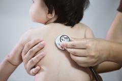 Soignez le bébé asiatique de examen et écoutez son battement de coeur Photo libre de droits