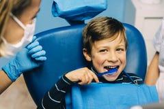 Soignez le dentiste enseignant un enfant à brosser des dents image stock