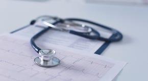 Soignez le lieu de travail avec un diagramme de cardiogramme de stéthoscope avec le disque médical de plan rapproché de table, pa Images libres de droits
