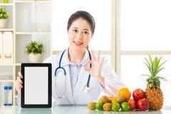 Soignez le nutritionniste avec des fruits tenant le comprimé numérique et le SI correct Images stock