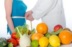Soignez le nutritionniste mesurant la taille d'un patient Image stock