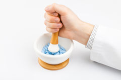 Soignez les pilules bleues de meulage avec l'aide du mortier et du pilon Photos stock