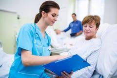 Soignez montrer le presse-papiers au patient dans la salle d'hôpital Photographie stock libre de droits