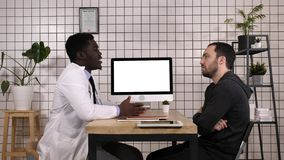 Soignez montrer les disques médicaux sur son ordinateur à son patient, il se dirige à l'écran Affichage blanc photographie stock libre de droits