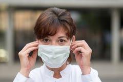 Soignez ou soignez porter un masque protecteur dehors Images libres de droits
