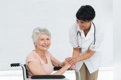 Soignez parler à un patient supérieur dans le fauteuil roulant Photographie stock