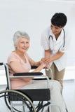 Soignez parler à un patient supérieur dans le fauteuil roulant Image stock