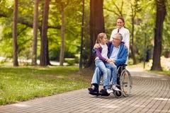 Soignez pousser l'homme supérieur sur le fauteuil roulant avec son jeune granddaugh Photos stock