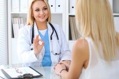 Soignez rassurer son patient féminin tout en montrant le signe correct Concept de médecine, d'aide et de soins de santé Photos libres de droits