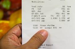 Soignez regarder le papier de l'analyse d'électrocardiogramme et vérifiez les symptômes du patient dans la chambre de secours Photographie stock libre de droits