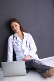 Soignez se reposer sur le plancher près du mur avec l'ordinateur portable Images stock