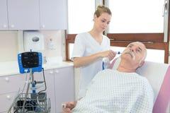 Soignez tenir l'otoscope et examiner l'homme supérieur d'oreille image libre de droits