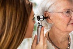 Soignez tenir l'otoscope et examiner l'oreille de la femme supérieure photos stock