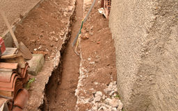 Soil excavation for pipe installation. Soil excavation for pipe laying in the basement royalty free stock photography