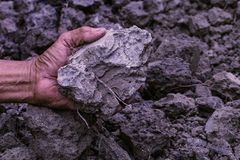 Soil in farmer man hands of black soil background. Soil is a mix. Ture of organic matter,minerals,gases,liquids, and organisms. it is a medium for plant growth Royalty Free Stock Image