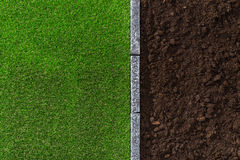 Soil and grass. Fertile humus soil and lush grass divided by a stone edging, gardening and landscaping concept royalty free stock photography