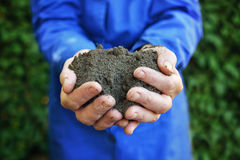 Soil in hands of agricultural worker Stock Image