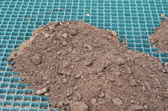 Soil for a new grass lawn is filled on a plastic lattice Royalty Free Stock Photo