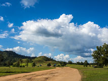 Soil road toward  green hill ,blue sky Stock Image