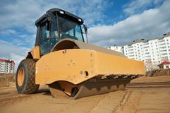 Soil vibration compactor at work. Soil vibration roller during sand compacting works at construction site Stock Photography
