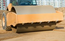 Soil vibration compactor at work. Soil vibration roller during sand compacting works at construction road site Stock Photo