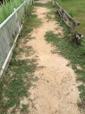 Soil and weeds path with wooden and metal fences in farm Stock Images