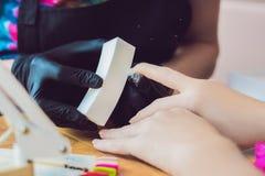 Soin d'ongle de doigt de plan rapproché par le spécialiste en manucure dans le salon de beauté Photographie stock