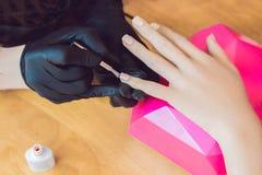 Soin d'ongle de doigt de plan rapproché par le spécialiste en manucure dans le salon de beauté Le manucure peint des ongles avec  Photographie stock libre de droits