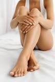 Soin de corps de femme Fermez-vous des longues jambes avec la peau et les mains molles Image stock