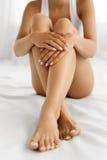 Soin de corps de femme Fermez-vous des longues jambes avec la peau et les mains molles Photographie stock libre de droits