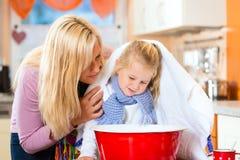 Soin de mère pour l'enfant malade avec le vapeur-bain Image libre de droits