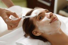 Soin de peau Belle femme atteignant le masque cosmétique le salon de station thermale photo libre de droits