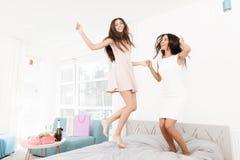 soin de Pré-mariage Filles à une poule-partie Les filles dans un voile sautent sur le lit Photo stock