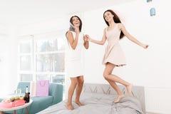 soin de Pré-mariage Filles à une poule-partie Les filles dans un voile sautent sur le lit Image libre de droits