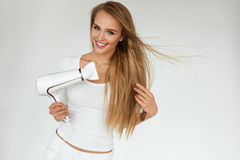 Soins capillaires Femme séchant de beaux longs cheveux blonds utilisant le dessiccateur image libre de droits