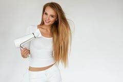 Soins capillaires Femme séchant de beaux longs cheveux blonds utilisant le dessiccateur photographie stock