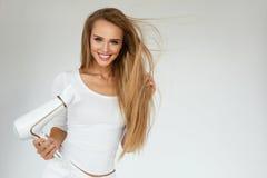 Soins capillaires Femme séchant de beaux longs cheveux blonds utilisant le dessiccateur image stock
