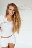Soins capillaires Femme séchant de beaux longs cheveux blonds utilisant le dessiccateur photographie stock libre de droits