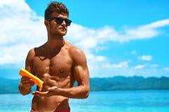Soins de la peau d'été Homme appliquant la lotion de corps de protection de protection solaire photographie stock libre de droits